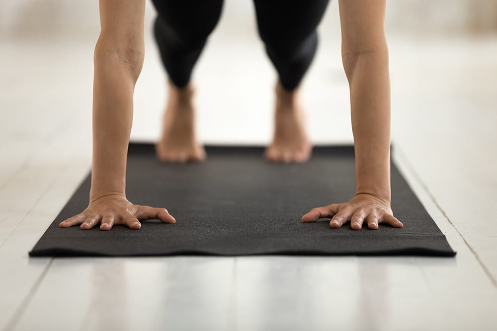 Young woman practicing yoga in plank pose