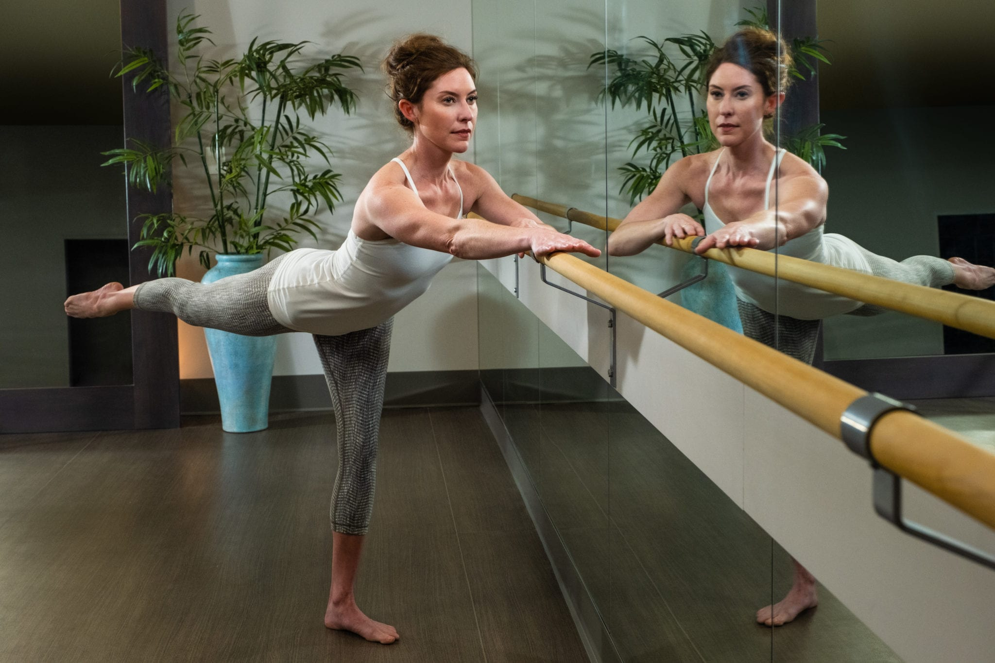 woman in barre class with leg extended while holding onto bar