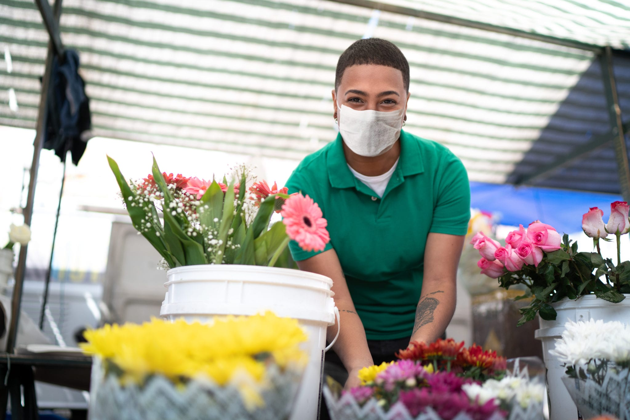 Portrait of a young florist working in a street market - with face mask