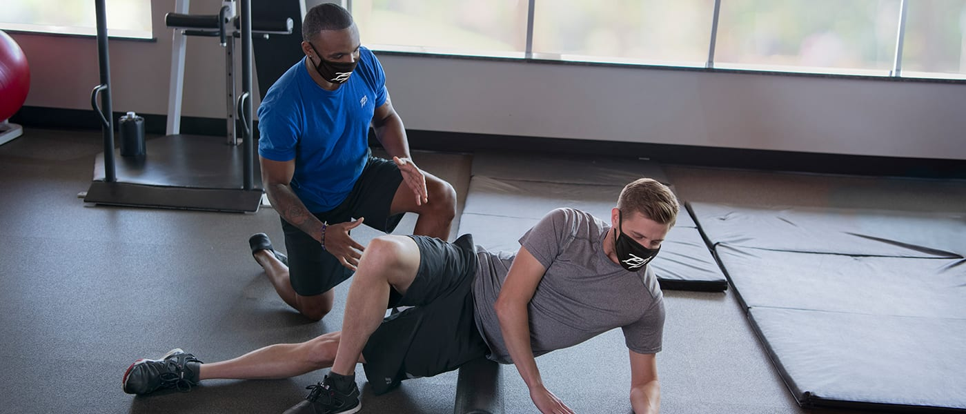gym member foam rolling with personal trainer providing proper technique for hips