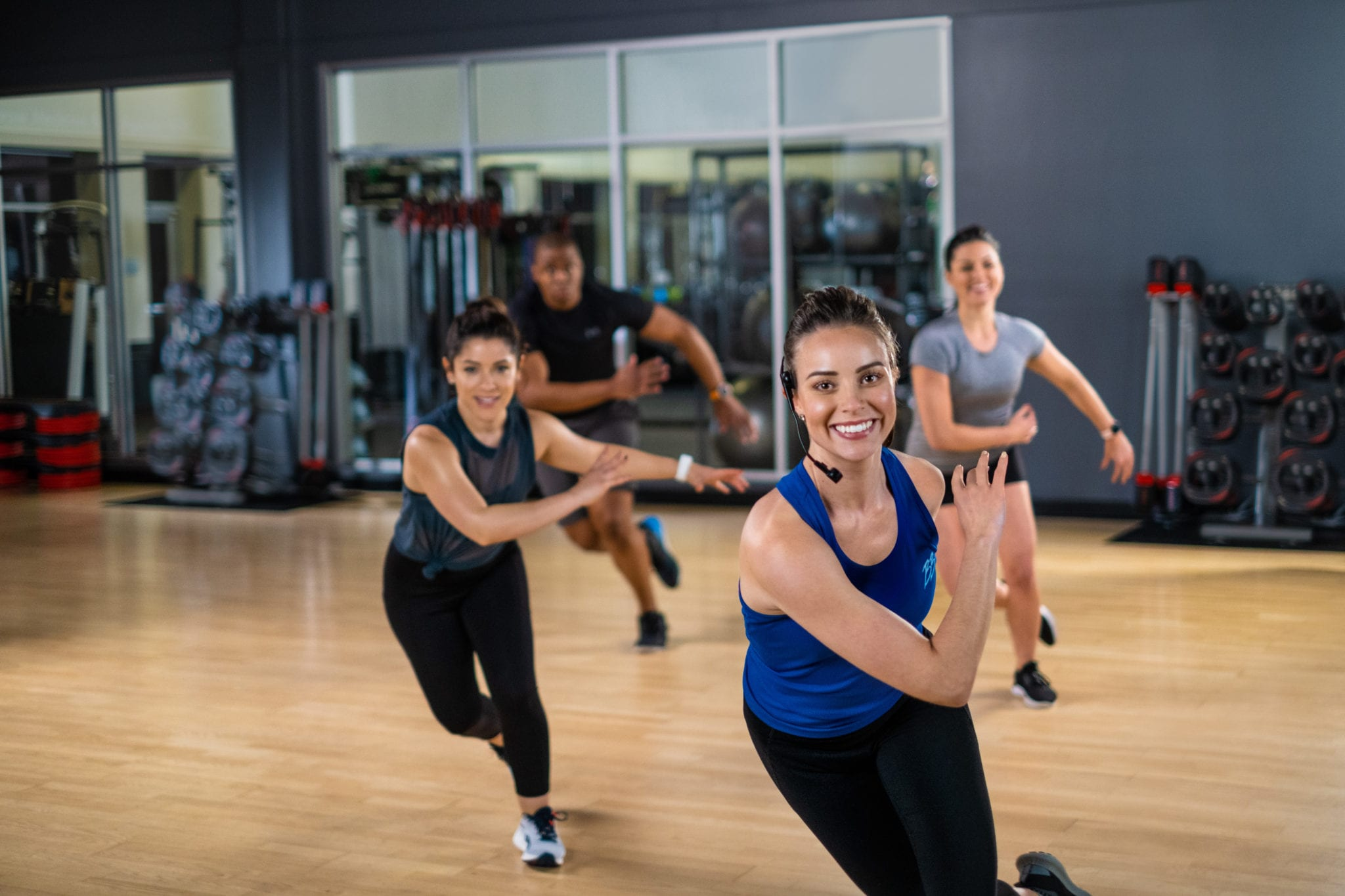 group instructor performing skate movement in fitness class at padonia gym studio