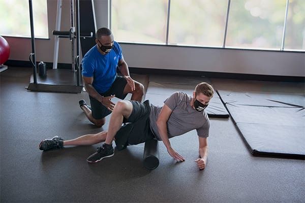 Male foam rolling at brick bodies with personal trainer