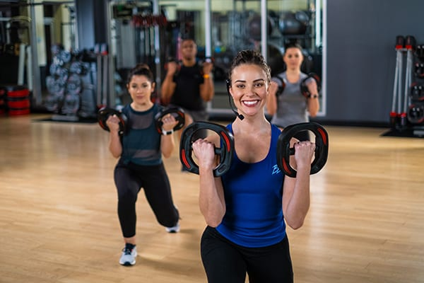 fitness instructor leading les mills group class
