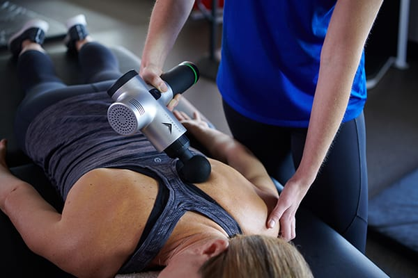 fitness member receiving massage gun therapy at gym
