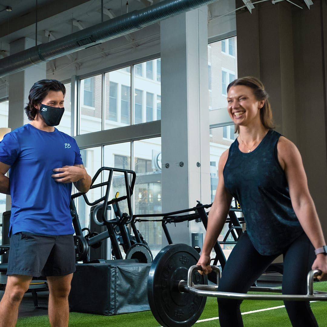 woman laughing while working out as instructor smiles and overlooks gym member technique