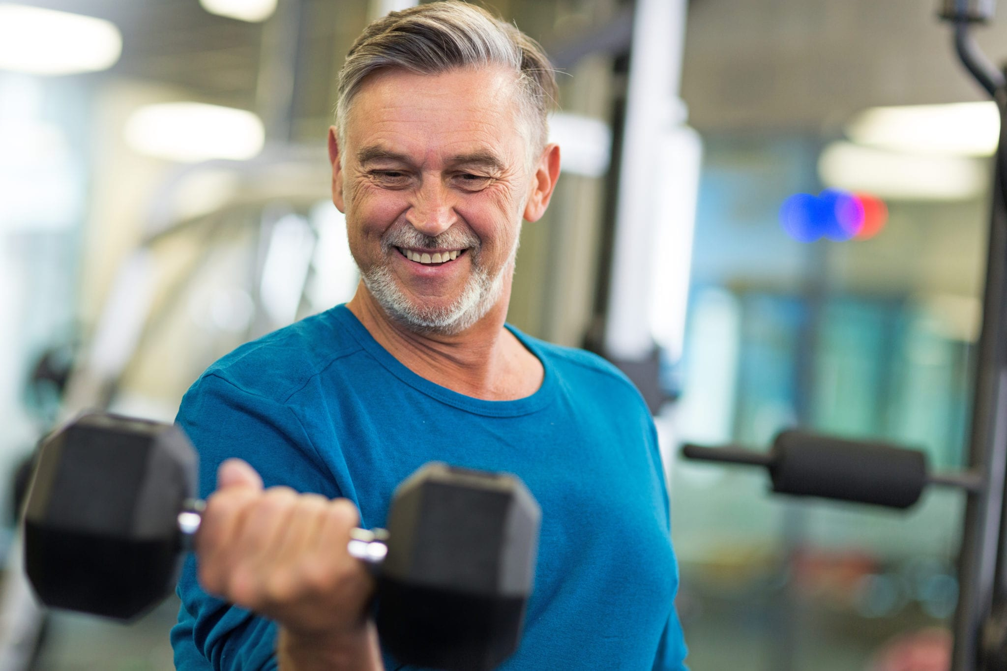 Senior man in health club curling weights with right arm