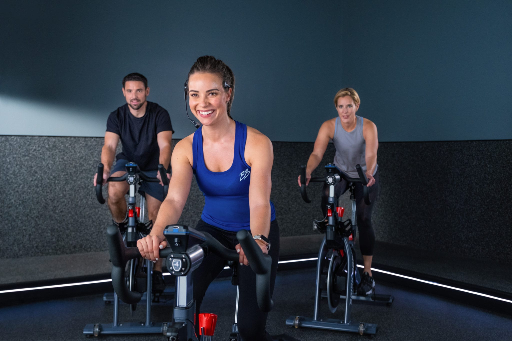spin instructor cheerfully leading cycling class in padonia brick bodies gym