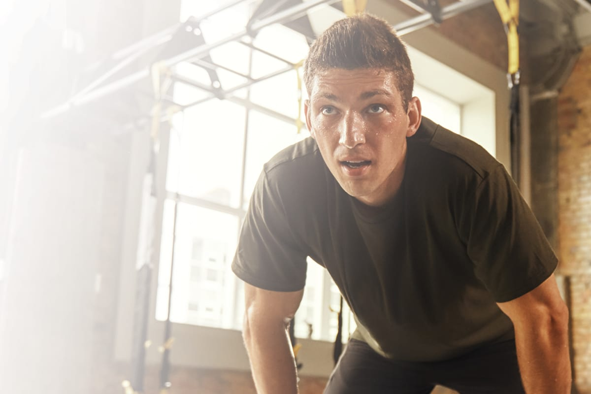 fitness member at health club leaning forward sweating after intense workout in gym