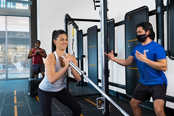 woman using fitness equipment to train while certified personal trainer coaches