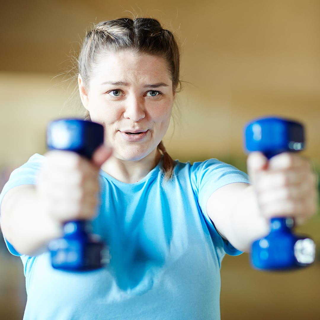 woman with blue shirt working out at gym with dumbells