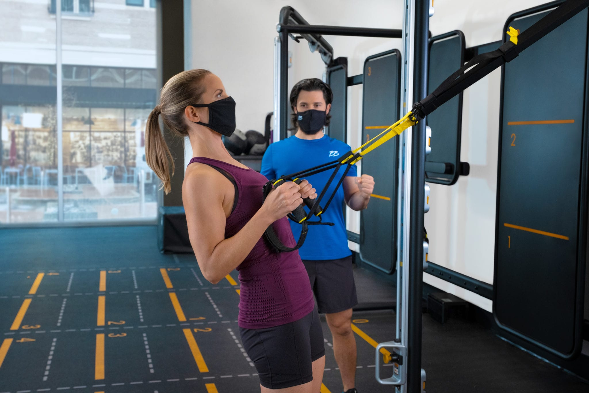 fit female gym member wearing mask using functional training arm equipment while personal trainer with mask advises in health club