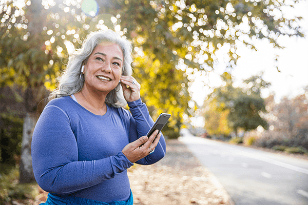 woman outdoors about to do cardio holding cellphone in one hand and putting her headphones in her left ear with the other hand